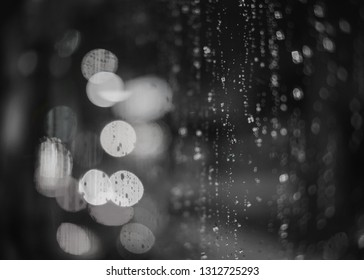 Monochrome black and white scene of a window with raindrops on it and bokeh lights in the background.