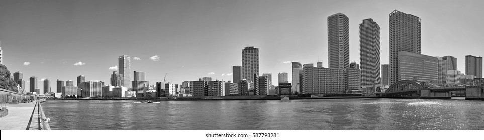 Monochrome black and white wide angle panoramic view of winter Sumida river under blue sky in Tokyo with wavy water, boats, bridge and skyscrapers