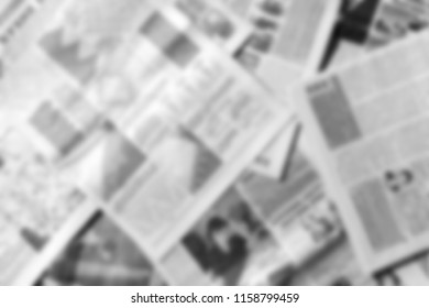 Monochrome blurred background of newspapers close-up.