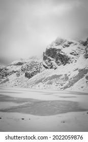 Monochrome Czarny Staw Gąsienicowy Lake view, High Tatra Mountains, Poland. Ice on the pond, snow on the rocks. Selective focus on Kościelec Peak, blurred background. - Shutterstock ID 2022059876