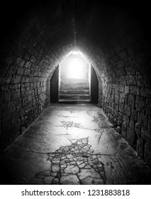 a monochrome dark image of an old underground pedestrian foot tunnel with an arched roofs stone walls and a cracked floor with a flight of steps steps leading to bright light at the end