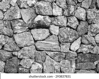 monochrome design decorative uneven cracked real stone wall texture and blackground