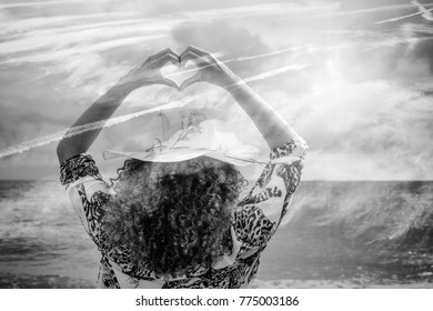 Monochrome double exposure of woman doing heart shape gesture with seascape and cloudscape