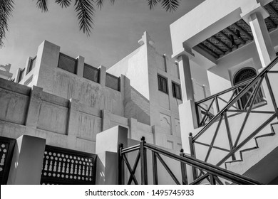 A monochrome, filtered image of buildings in a Middle Eastern heritage area of restored traditional arabian houses with shuttered windows and white plasterwork.