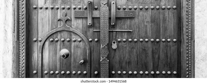 A monochrome, filtered image of a carved wooden door and lock at the entrance to a restored traditional arabian house.