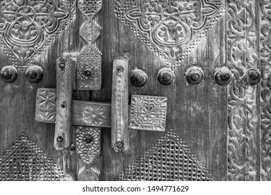 A monochrome, filtered image showing detail of a carved, wooden, traditional lock at the entrance to a restored traditional arabian house.