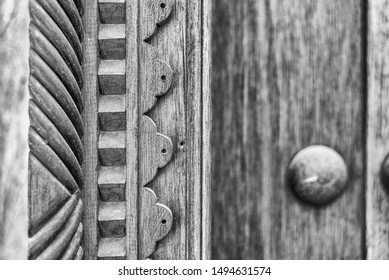Monochrome, filtered, narrow-focus detail of a carved wooden doorframe at the entrance to a restored traditional arabian house.