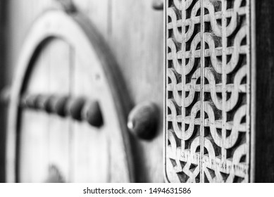 Monochrome, filtered narrow-focus detail of a carved wooden door at the entrance to a restored traditional arabian house.