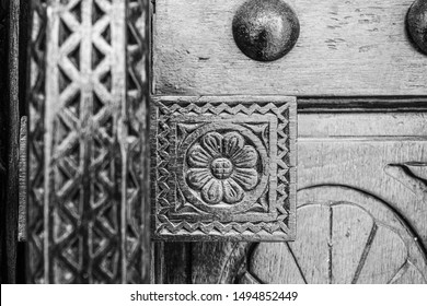 Monochrome, filtered, narrow-focus image of a carved detail of a wooden door at the entrance to a restored traditional arabian house.