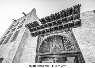 Monochrome, filtered view of the elaborately carved roof and doorway of an entrance and tower of a arabian merchant's traditional house in the MIddle East.