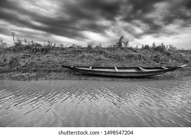 A monochrome, filtered view of a fishing boat resting on riverbank vegetation of a rural canal under a cloudy sky.