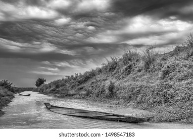 A monochrome, filtered view of sunken fishing boats rest in a rural canal under a cloudy sky