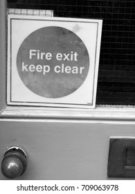 Monochrome fire exit keep clear mandatory self adhesive sticker on rear entrance door to retail unit
