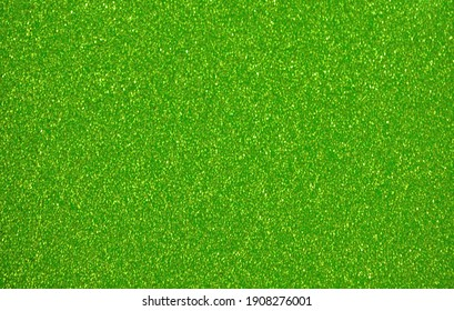 Monochrome green surface with small splashes of golden color with blurred background. Background, pattern, texture.