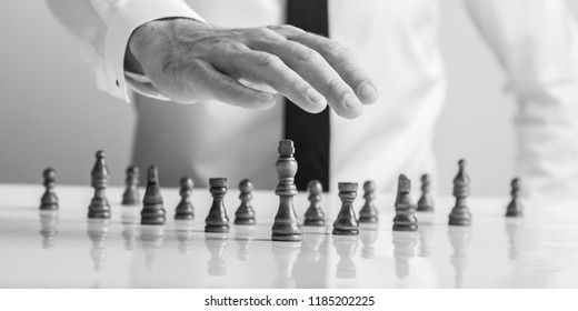 Monochrome image of a businessman holding his hand above wooden chess pieces with king in the front in a conceptual image of business leadership and power.