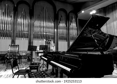 Monochrome image of an empty concert hall stage with musical instruments piano drums.