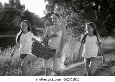 Monochrome image of happy mother with daughters walking at meadow