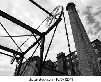 monochrome image of the historic canal chain bridge in Huddersfield West Yorkshire with large old mill building with a tall stone chimney against a blue sky with clouds