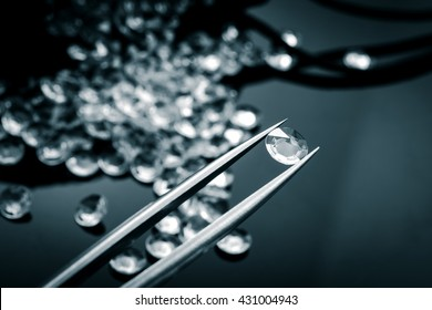 Monochrome image of a jeweler inspecting with tweezers one diamond of the many diamonds in a pile that spilled from a bag