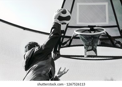 Monochrome Image of a Kid Shooting a Basketball Through a Trampoline Mounted Basketball Hoop