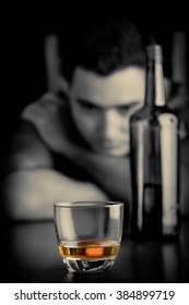 Monochrome image of a lonely and sad man drinking alone