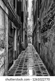 monochrome image of a long narrow urban alley with wet cobbles and old eroded walls in venice italy