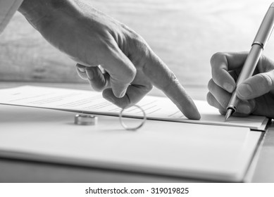 Monochrome image of male hand pointing to a woman where to sign legal divorce papers or marriage registry with wedding rings on the document.