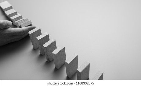 Monochrome image of a male hand stopping domino effect in a business challenge and solution concept.