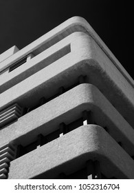 monochrome image of an old brutalist concrete tower block with rounded textured corners against a dark sky