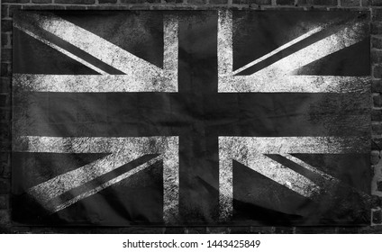 monochrome image of an old stained dirty union jack british flag with dark crumpled edges on a brick wall background