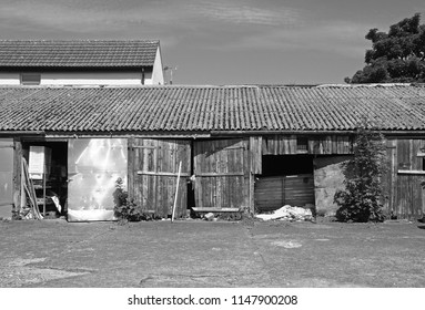 monochrome image of patched and repaired scruffy rural workshop out buildings with shabby broken wooden doors with peeling faded red paint rubbish on the ground and asbestos roof