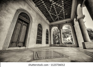 A monochrome image of a porch with carved doors and window shutters and tiled flooring at the entrance to a restored traditional arabian house.