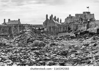 Monochrome image of the seabed around Elizabeth Castle in St Aubin's bay on the island of Jersey at low tide with the seabed in the foreground