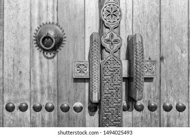 A monochrome image showing detail of a carved wooden door, handle and lock at the entrance to a restored traditional arabian house.