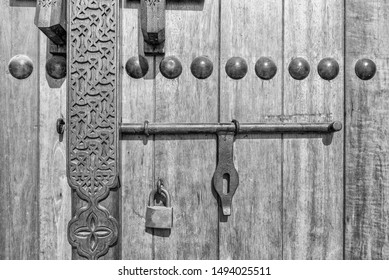 A monochrome image showing detail of a carved wooden door and lock at the entrance to a restored traditional arabian house.