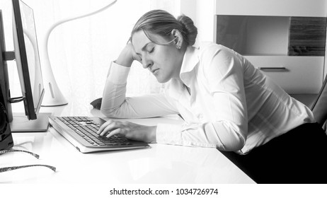 Monochrome image of tired sleepy businesswoman at office