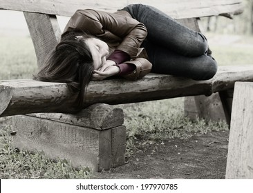 Monochrome image of a woman lying curled up sleeping on a rustic wooden park bench, conceptual of homelessness, exhaustion and loneliness