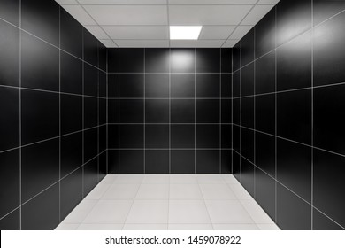 Monochrome interior with tiled black walls and white floor. There is a luminous lamp on the ceiling which reflected on the glossy walls. Horizontal.