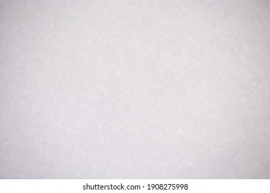 Monochrome light gray surface with background blur and vignetting. Background, pattern, texture.