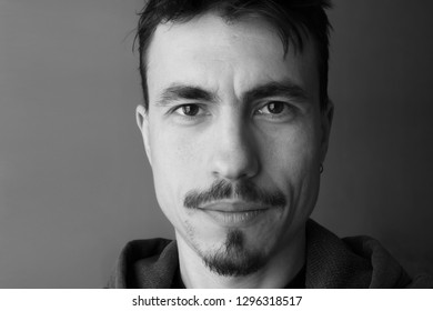 Monochrome male portrait closeup. Portrait of the man with mustache and beard. Confident male look. Textured portrait of the young man. Black and white studio portrait