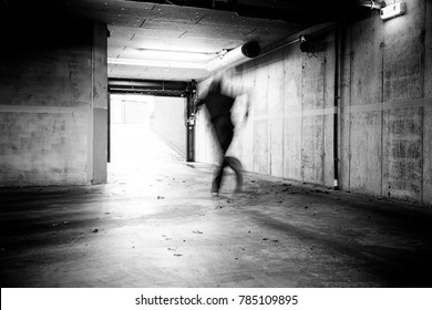 Monochrome of a man fleeing a grungy underground parking.