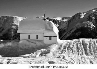 Monochrome of mountain chapel with a backdrop of high mountains, covered in snow