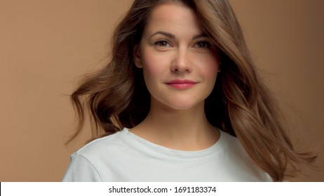 Monochrome natural makeup look Caucasian woman in studio in white t-shirtwith healthy shiny hair blowing Calm watching straight to camera