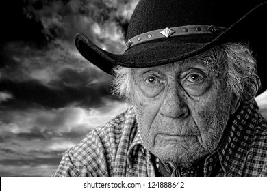 monochrome of an old man wearing a black felt hat against a stormy cloudy sky