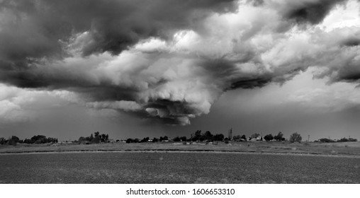 Monochrome of ominous and menacing looking funnel cloud on a stormy day over the populated area