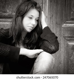 Monochrome outdoor portrait of a sad teenage girl looking thoughtful about troubles