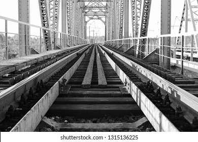 monochrome photo of the bridge on the railroad tracks and industrial gray stone