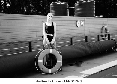 monochrome photo of gorgeous young woman in swimsuit and swimming cap posing with lifebuoy