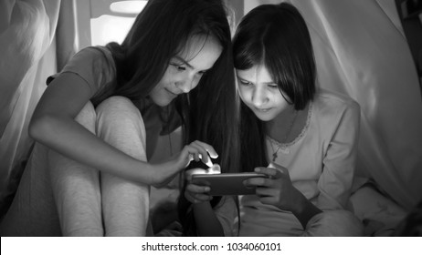 Monochrome photo of two teenage girls playing on mobile phone at night - Shutterstock ID 1034060101