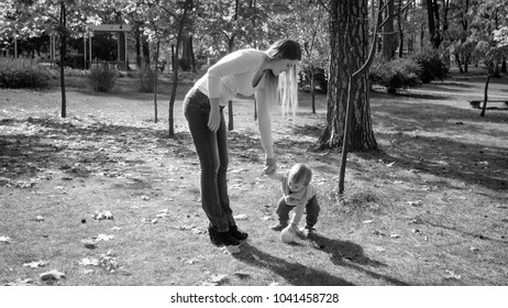Monochrome photo of young mother playing in park with her toddler son